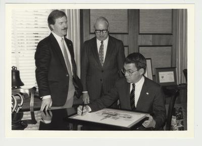 President Roselle (seated on the right) signing a drawing of Memorial Hall and other buildings on the University of Kentucky campus.  Jay Brumfield, Director of the Alumni Association, is standing in the center of the photo