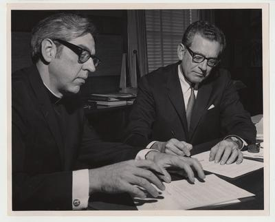President Singletary (seated, right) is signing an University of Kentucky - Thomas Moore Agreement with an unidentified Catholic priest