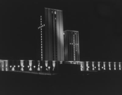 A color photo of the Kirwan-Blanding Complex at night, with the windows of the towers lit-up in the shape of a cross