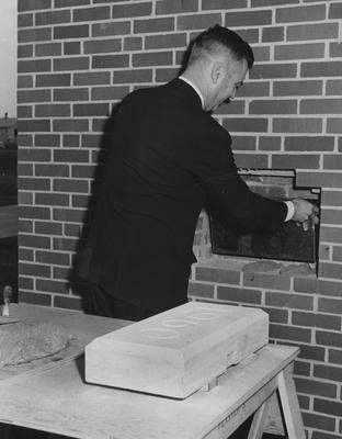 President Frank Dickey getting ready to put the 1960 block on Blazer Hall. This photograph received October 16, 1960 from Public Relations