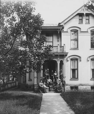 A group of unidentified people on the front steps of the Carr Boarding House. Carr is the name of the owner of the house