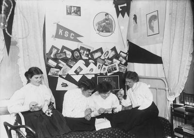 Four unidentified women in a dorm room in 1908. During this time there were four to five women in a room and lights-out by 10 or 11p.m. Photographer: R. R. Rodney Boyce and Associates