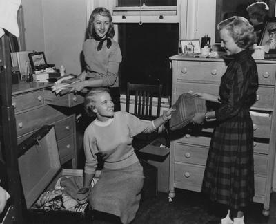 Three women either packing or unpacking a trunk. From left to right: Jerry Kelley, Betty Clay, and Benita Boyd. During the 1950's upper-class women had a curfew of 10:30p.m. on the weekdays and 11p.m. on the weekends. Photographer: Lexington Herald-Leader