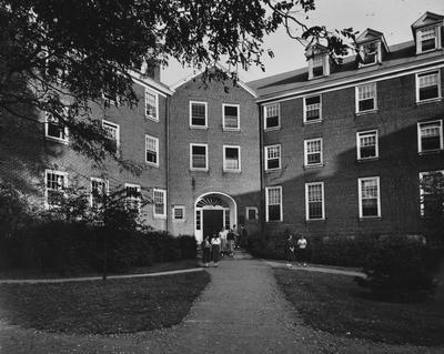 Seven unidentified women walking out of Boyd Hall, a woman's dormitory. Boyd Hall was built in 1925 and was named after Cleona Boyd