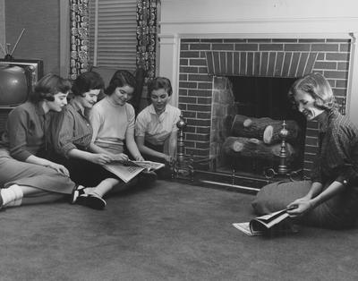 Five unidentified women are sitting in the living room, around a fire place in Boyd Hall, a woman's dormitory. Boyd Hall was built in 1925 and was named after Cleona Boyd