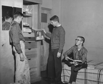 Three unidentified men are looking at a picture of a woman in a Donovan Hall dorm room