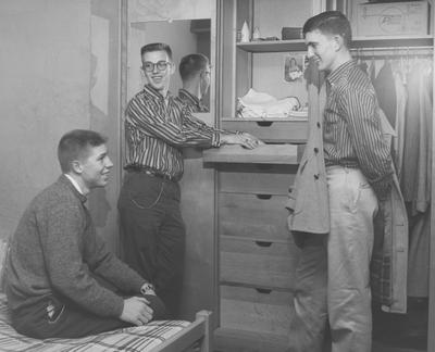 Three unidentified men are talking in a Donovan Hall dorm room