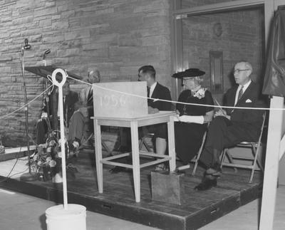 President Frank Dickey (third from right), Sarah Bennett Holmes (Dean of Women, second from right), and three unidentified men are seated on stage at the dedication of Holmes Hall on May 25, 1958. Received May 25, 1958 from Public Relations