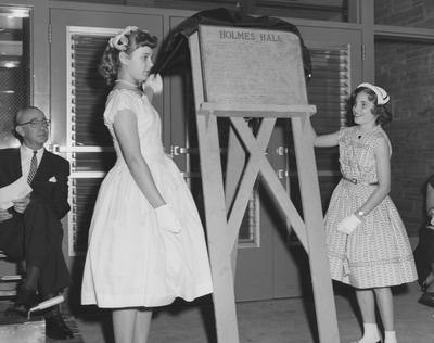 Sarah Bennett Holmes' granddaughters reveal the plaque for Holmes Hall at the dedication on May 25, 1958. Received May 25, 1958 from Public Relations