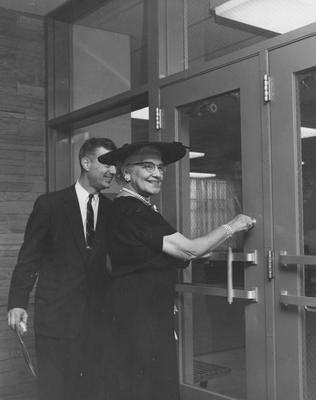 President Dickey and Sarah Holmes are unlocking the doors to Holmes Hall at the dedication. Received May 25, 1958 from Public Relations