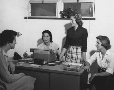 Four unidentified women are seated around a desk in Holmes Hall. Photographer: University of Kentucky. Received November 18, 1958 from Public Relations