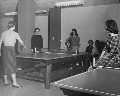 Four unidentified women are watching two unidentified women playing ping pong in Holmes Hall. Photographer: University of Kentucky. Received November 18, 1958 from Public Relations