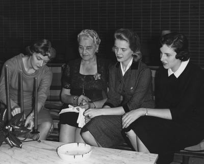 Katherine Maddox-Broadbent (second from right) and two unidentified women are seated with Sarah Bennett Holmes (second from left) in Holmes Hall. Received December 5, 1958 from Public Relations
