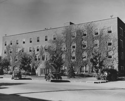 Cars parked in front of Jewell Hall, a women's residence hall, and an unidentified woman is entering the building. Jewell Hall was named after Mary Frances Jewell. Photographer: W. E. Sutherland