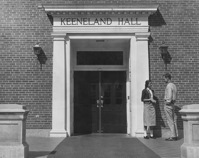 Ann Shirley Gillook (Miss Kentucky 1957) is talking to a young man at the entrance of Keeneland Hall, a woman's dorm. Keeneland Hall was named after the Keeneland Foundation which donated $200,000 and on October 17, 1955, it was dedicated to the foundation. This photo appears on page 22 of the 1956-1957