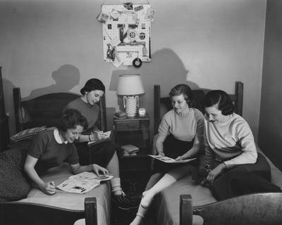Nancy Graves and three unidentified women are sitting on two beds in Patterson Hall, UK's first woman dorm. Patterson Hall was completed in 1904 and was named after James K. Patterson. Received March 16, 1957 from Public Relations