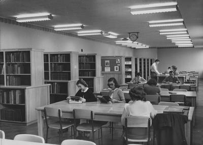 Students studying in the Fine Arts Library in the Fine Arts Building. (library was later relocated) Miss Algie Dickson is seated at the desk.  Photographer: John B. Kuiper