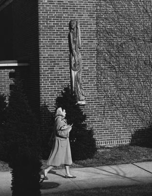 An unidentified woman is walking past the side of the Fine Arts Building, where there is a wooden sculpture on the building