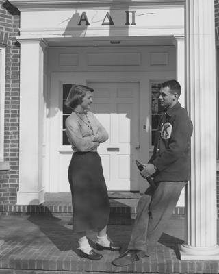 An unidentified woman in talking to an unidentified man in front of the Alpha Delta Pi House