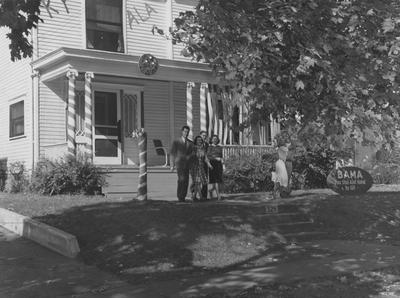 Mary Virginia Fulcher (far right) and three unidentified people are walking from the Delta Delta Delta house on 329 Aylesford Avenue. Received June 13, 1959 from the Cincinnati Enquirer