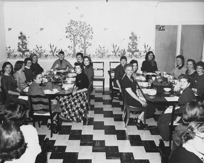 Unidentified women are seated at tables, possibly at a mother-daughter luncheon in the Zeta Tau Alpha house. The Zeta Tau Alpha sorority is no longer on campus and since the late 1980's, the house was leased by Sigma Kappa sorority