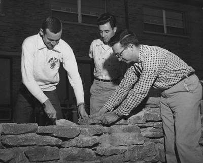 Three unidentified men are constructing a stone wall