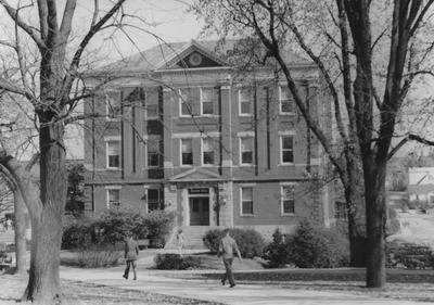 Unidentified people walking by Frazee Hall. Frazee Hall was built in 1907 and named after David Frances Frazee on June 3, 1931. On January 24, 1956, the building was partially destroyed by a fire. Photographer: John Sutterfield