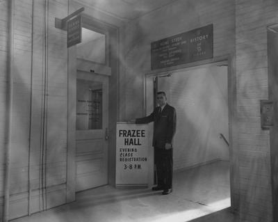 An unidentified man is is standing beside a sign by Frazee Hall. Frazee Hall was built in 1907 and named after David Frances Frazee on June 3, 1931. On January 24, 1956, the building was partially destroyed by a fire