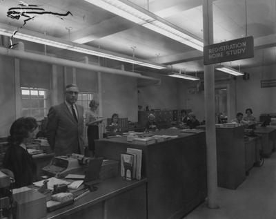 Unidentified people are working in the Home Study registration area, now called Independent Study, located in Frazee Hall. Frazee Hall was built in 1907 and named after David Frances Frazee on June 3, 1931. On January 24, 1956, the building was partially destroyed by a fire
