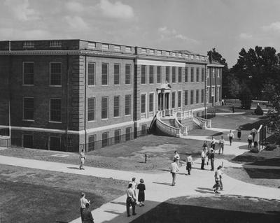 Unidentified students are walking past the Journalism Building. The Journalism Building was dedicated on November 2, 1951 and named after Enoch Grehan. It is also the home to the independent student newspaper,