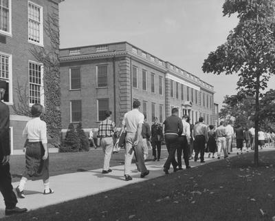 Unidentified students are walking past the Journalism Building in the 1957