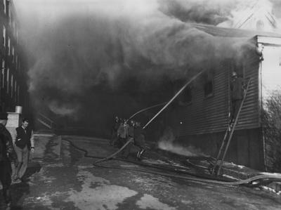 Firefighters trying to extinguish the fire. Guignol, on January 10, 1947, engulfed in flames. Photographer: W. E. Sutherland