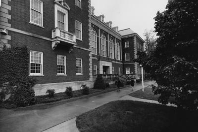 Second front entrance created as a result of increased enrollment and need to enlarge the entrance to accommodate the increased student use of this main library. The ornate arched doorway was removed and replaced with a squared entrance with double doors. The original porch remained. Also sidewalks have been added for easier access to the library