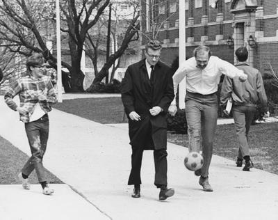 Three unidentified men kicking a ball on the sidewalk in front of the M. I. King Library. This photo appears second on page 195 of the 1969