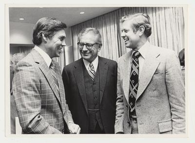 From the left:  Cliff Hagan, Athletic Directory; President Singletary; and an unidentified man.  The location is Madisonville and Owensboro