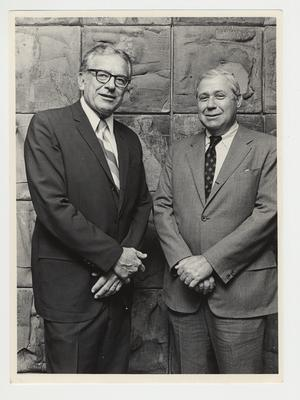 President Singletary (left) is standing with Richard Cooper (right) at a Board of Trustees meeting