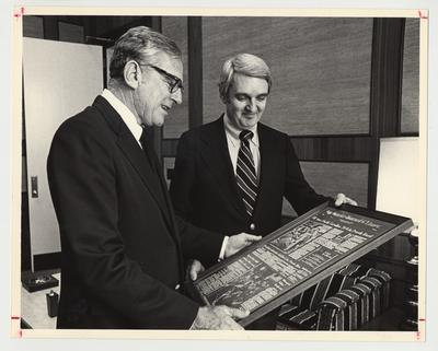President Singletary receiving a framed article / plaque about the University of Kentucky's 1976 Peach Bowl victory over North Carolina from The Courier Journal and Times Vice President for public affairs, Donald B. Towles