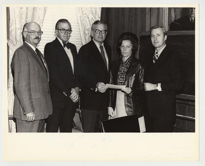 President Singletary (third from left) is standing with four unidentified people and handing something to an unidentified woman