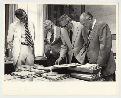 President Singletary is standing and looking at an oversized book.  From the left:  Dr. Hornback, University of Kentucky Vice President; Charles Thomas; President Singletary; and Earl Wilson Sr., Board of Trustees Member and Vice President of Central Bank, Lexington and Kentucky Insurance Company.  The title of the book is