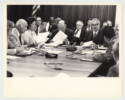 President Singletary is (right) seated at a table with unidentified people, reviewing documents and speaking at an unidentified meeting