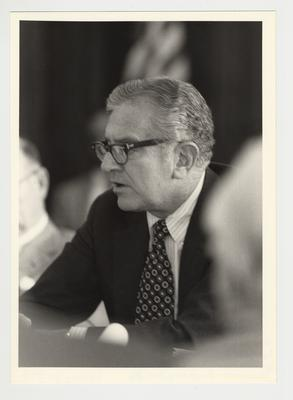 President Singletary seated at a table and talking at an unidentified meeting