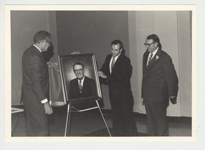 President Singletary (left) and Charles Wethington (center) are unveiling the portrait of Stan Wall.  Stan Wall (right) is watching the proceedings.  Stan Wall was the Vice President of the Community College System and he retired in 1981