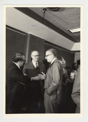 President Singletary (right) is standing and conversing with two unidentified men at the 1982 Coal Company Party which was held at the Hyatt Regency in Lexington, KY