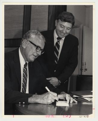President Singletary (seated, left) is signing a piece of paper while John Bryant (standing, right), Assistant Director of the Library Department and head of the United Way drive at the University of Kentucky, watches