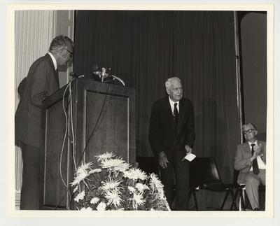 From the left:  President Singletary; Dr. Thomas Clark, retired history professor; Paul Willis, Director of Libraries and a graduate of the University of Kentucky Law School.  It appears as though President Singletary (at a podium) is introducing Dr. Clark, who is standing.  They are at the 2,000,000 book celebration