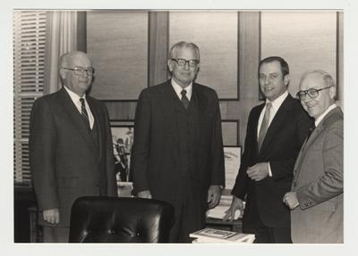 President Singletary is standing with three men in an office.  From the left:  unidentified man, President Singletary, Charles Wethington, and unidentified man