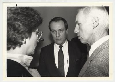 President Charles Wethington (standing, center) is conversing with Carolyn Brott (left) and Mr. Leigh (right) during a UK vs Florida game