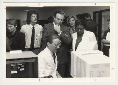 President Wethington with Bradley Bryan (seated), second year medical student; Juanita Fleming (right of Wethington), Dean of the College of Nursing; and Janet Stith (far left), Director of the Medical Library.  There are also several unidentified people.  Everyone is looking at a computer in the Pathology Department.  Communi-K