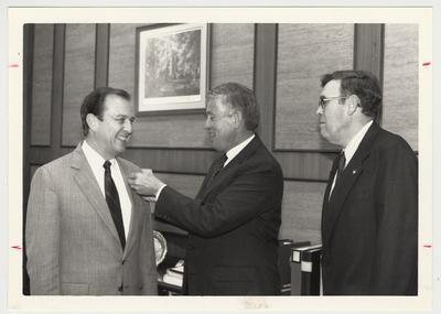 UK Central Development.  John Zachem (center) gives Fellows pin to Charles T. Wethington, Jr. (left) while Lou Swift watches (right).  Communi-K