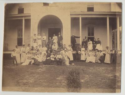James White is standing on the porch and leaning against a post wearing a black suit.  The photograph is of the White Family Reunion and contains many unidentified people
